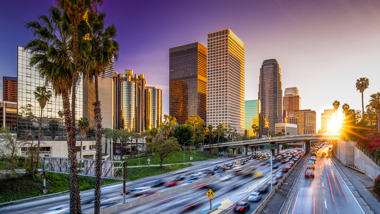 Los Angeles downtown skyline behind highway during sunset