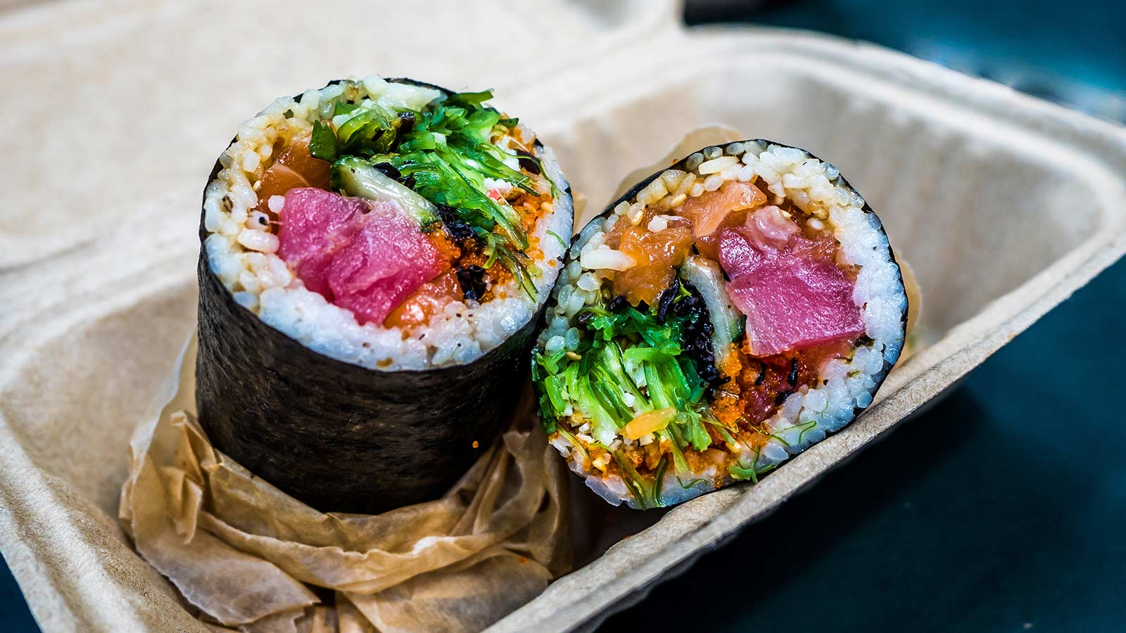 Japanese fusion sushi burrito in takeout container