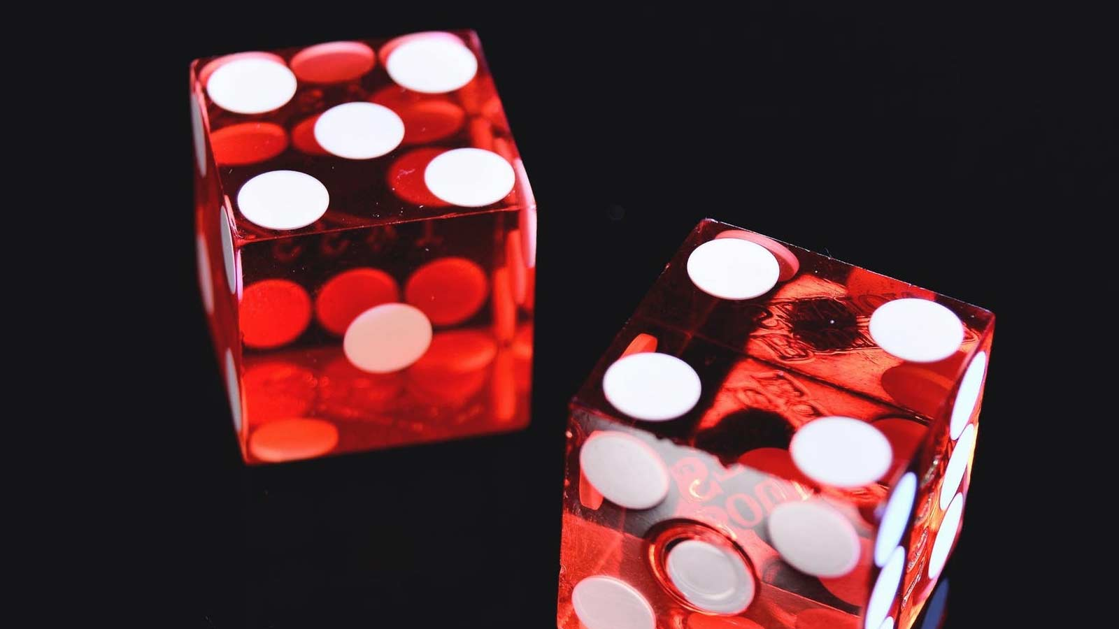 Two red dice against a black background