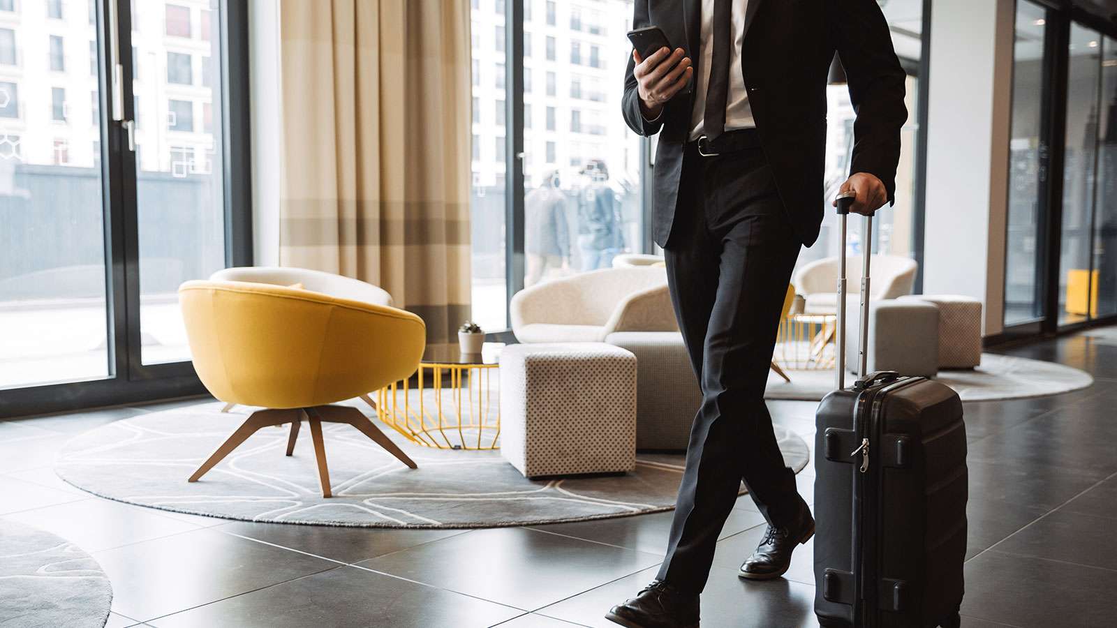 Man walks with luggage through hotel lobby